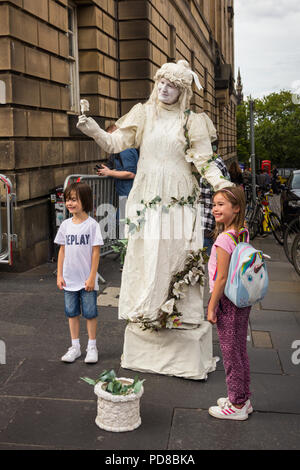 Edinburgh, Scotland, UK. 7th August 2018. One woman performs as a living statue, interacting and posing with two young children. Street acts and artists, alongside promoters of Fringe Festival events, ply the streets of Edinburgh Festival, providing entertainment and amusement to the many visitors to the Fringe. Credit Joseph Clemson, JY News Images/Alamy Live News. - Stock Image