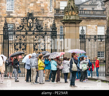 Holyrood, Edinburgh, Scotland, United Kingdom, 12th August 2018. UK Weather: the rain and mist as the remnants of Storm Debby hits the capital does not deter tourists at Holyrood Palace in front of the large ornate gate. People queuing to enter the palace holding umbrellas - Stock Image