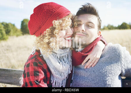 Romantic young couple of a beautiful blonde woman with curly hair and wearing a red wool cap hugs to her boyfriend and a handsome man outdoor - Stock Image