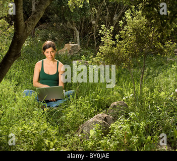 woman in her 40's sitting with a laptop in nature - Stock Image