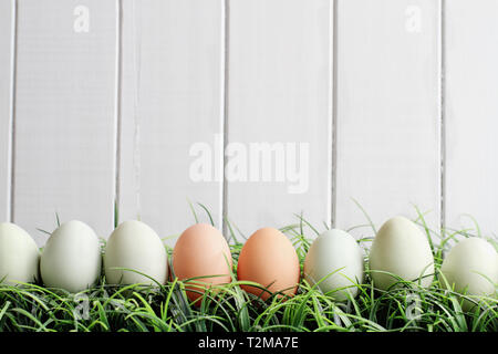 Natural colored Easter eggs in grass against a white wooden background with room for copy space. - Stock Image