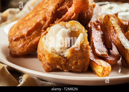 Traditional fish in beer batter and chips with green pea and tartar sauce - Stock Image