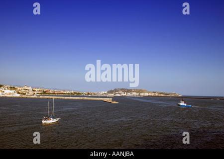 Cagliari skyline and Yacht Sardinia tug yacht sailing boat sail sailboat Cagliari Sardinia skyline town city skyline cityscape - Stock Image