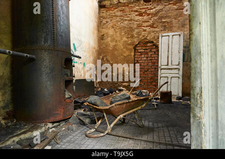 Neglected facilities with rusty metal boiler and wheelbarrow with coal bricks at the Canfranc International railway station (Huesca,Aragon,Spain) - Stock Image