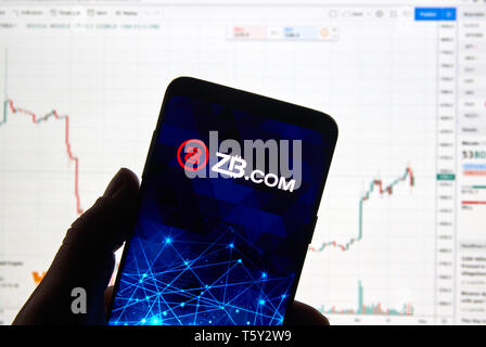 MONTREAL, CANADA - APRIL 26, 2019: ZB.com cryptocurrency exchange logo and application on Android Samsung Galaxy s9 Plus screen in a hand over a lapto - Stock Image