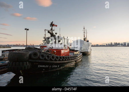Tug boat docked at Lonsdale Quay with the Vancouver skyline beyond, North Vancouver, BC, Canada - Stock Image