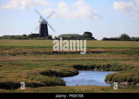 Tower Mill Burnham Overy across marsh land near the North Norfolk coast. - Stock Image