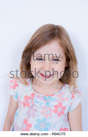 portrait of three years old blonde girl, with white dress with red and blue flowers  looking and smiling, standing isolated in white background - Stock Image