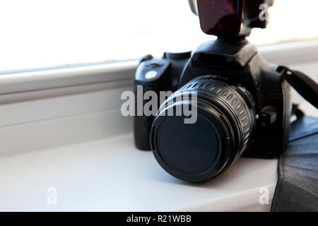 Camera and flash and strap in the window with copy space - Stock Image