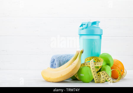 Fitness and healthy food concept. Dumbbells, fruits and drink bottle on wooden table. With copy space for your text - Stock Image
