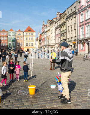 Young children boys and girls watching a street entertainer in the cobbled  old town square in the Polish city of Poznan Poland - Stock Image
