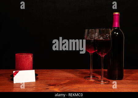Beautiful etched wine glasses and bottle of red wine, red candle on wooden table with name tag on dark background. Valentines, Mothers Day, Easter, Ch - Stock Image