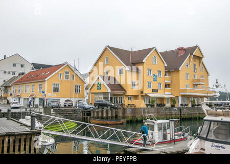 Floro, Norway, July 23, 2018: Yellow Quality Hotel building is situated next to local marina. - Stock Image