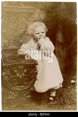 A small boy, John Cooper, wearing a white knitted coat. - Stock Image