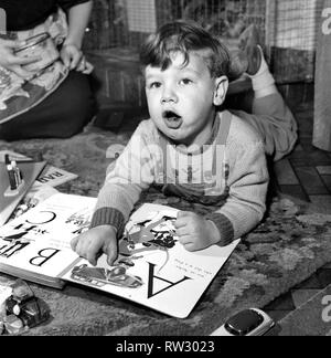Small boy reading book. Gerry Michael (2) - Car Expert. November 1952 C5495 - Stock Image