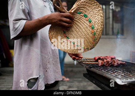 A street vendor cooks skewered chicken parts on a charcoal grill in Baclaran, Manila, Philippines. - Stock Image