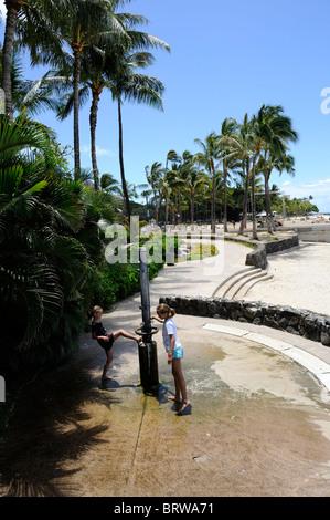 2 children (8 years old, 11 years old) using open-air shower on Waikiki Beach, Waikiki, Honolulu, Hawaii - Stock Image