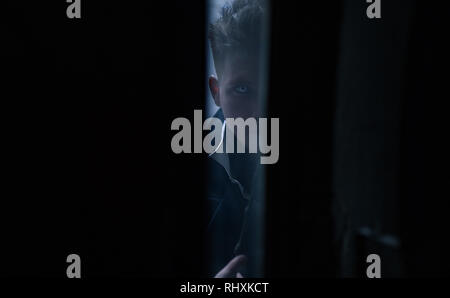 Portrait of young man in image of black magician with magic wand in his hand. Closeup. - Stock Image