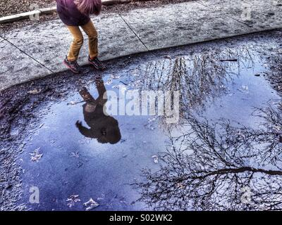 Boy and trees reflected in puddle of water - Stock Image