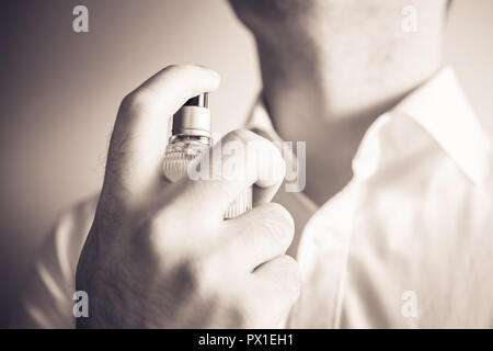 Businessman Using An Eau De Parfum Spray Bottle On His Neck, Monochrome Colors - Stock Image