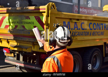 Construction worker directs tipper lorry as it backs up to drop its load - Stock Image