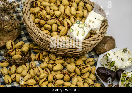 Fried pistachios with persimmons and nougat in a wicker basket and on a white plate next to the stones and dried flowers on paper with blue squares - Stock Image