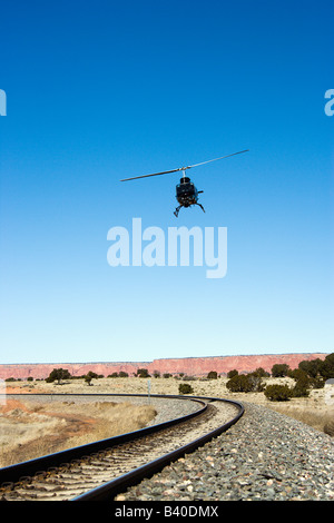 Low angle shot of helicopter flying over train tracks - Stock Image