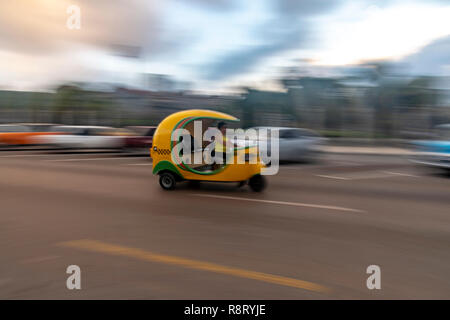 Cuban woman driving a speeding bright yellow Coco Taxi in Havana Cuba - Stock Image