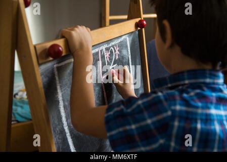 Close-up of a boy writing on a blackboard, Munich, Germany - Stock Image