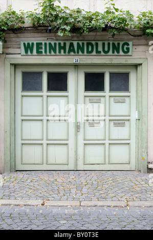 Eingangsbereich einer Weinhandlung mit Schild und Weinranke. - Entrance area of a wine shop with sign and vine tendril. - Stock Image