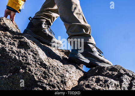 Close up of hiker legs and shoes rocking the mountain helping with one hand - concept of outdoor leisure activity and sport lifestyle - adventure and  - Stock Image