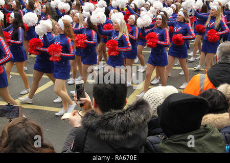 London, UK. 1st January, 2019.  People watch and photograph the Varsity Spirit All-Americans-Group #3 on the parade route. About 8,000 performers representing the London boroughs and over 20 countries from across the globe take part on the annual New Years Parade on the street of London on January 1, 2019. The parade will as is custom include dancers, acrobats, cheerleaders, marching bands, historic vehicles and huge balloons making their way from Green Park Tube station to Parliament Square. Credit: david mbiyu/Alamy Live News - Stock Image