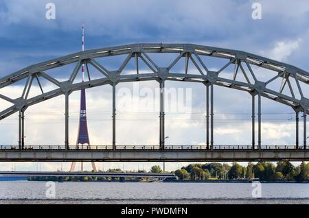Railway bridge, Riga, Latvia, over the Daugava river, with the Radio and TV tower in the background - Stock Image
