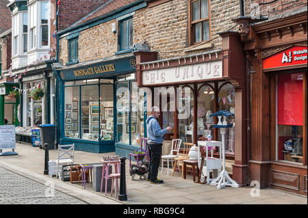 Bishop Auckland, County Durham, UK. A man looks at his mobile outside an art gallery and antique shop in the historic Fore Bondgate street - Stock Image