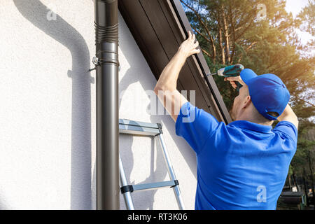 roofer installing metal roof drip edge profile - Stock Image