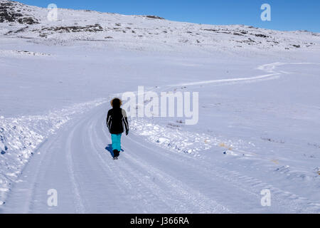 a person walking on a snowy road - Stock Image
