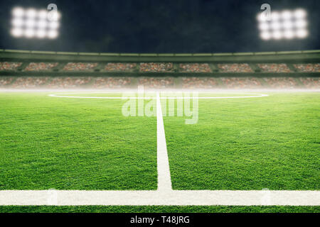 Low angle view of soccer stadium field with blurred crowd background and copy space. - Stock Image