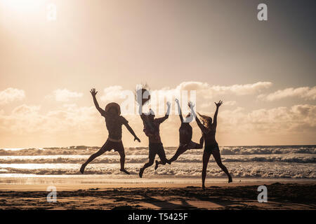 Group of people jump happy together at the beach during sunset with sky in background and silhouette bodies - summer vacation holiday for friends peop - Stock Image