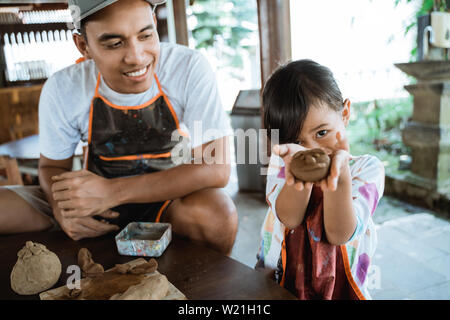 asian dad and his child showing what they make with clay in pottery workshop - Stock Image
