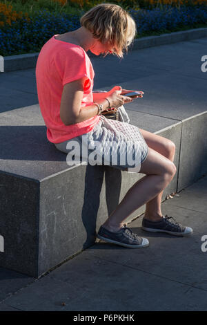 Young woman with blond hair sitting on park bench in evening sunshine working on her mobile phone in Place de l'Hotel de Ville St Quentin France - Stock Image
