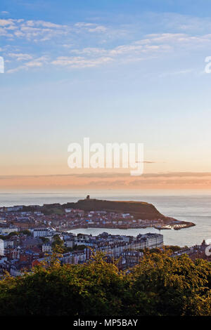 Scarborough's Castle headland and harbour at sunrise, seen from the summit of Oliver's Mount. - Stock Image