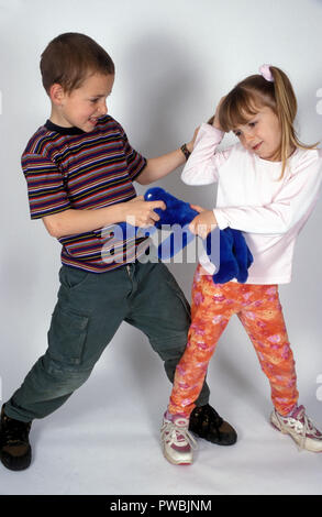 brother & sister fighting over a toy - Stock Image