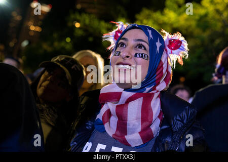 Muna Hussaini of Austin listens as former congressman Beto O'Rourke of El Paso, TX kicks off his presidential campaign at a late-night rally in front of the Texas Capitol. - Stock Image