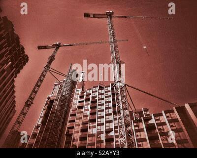 A skyward view from the ground looking up at the construction of a high rise building that will contain housing and retail units. An increasing population means housing is always required. © C.HOSKINS - Stock Image