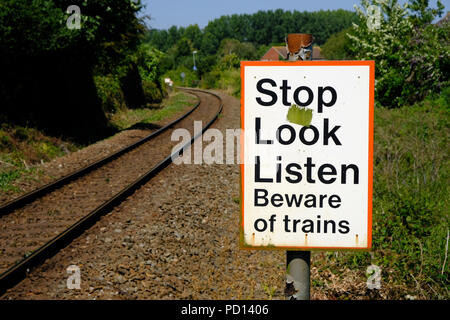 A Stop Look Listen sign warns pedestrians of passing trains at a crossing point, Exmouth, Devon, UK - Stock Image