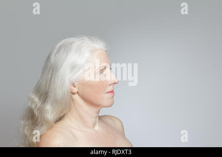 Side view of a mature woman with shiny long white hair, but without make-up, gray background, copy space. - Stock Image