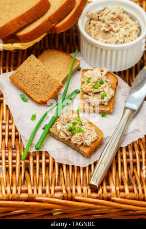 Toast of rye bread with fish pate (rillettes) of smoked  mackerel, cream cheese and green onions . Gourmet appetizer. Picnic. Selective focus - Stock Image