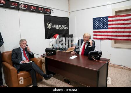 U.S. President Donald Trump and National Security advisor John Bolton, speak by phone with Iraq Prime Minister Adil Abdul-Mahdi during a surprise visit to Al Asad Air Base December 26, 2018 in Al Anbar, Iraq. The president and the first lady spent about three hours on Boxing Day at Al Asad, located in western Iraq, their first trip to visit troops overseas since taking office. - Stock Image