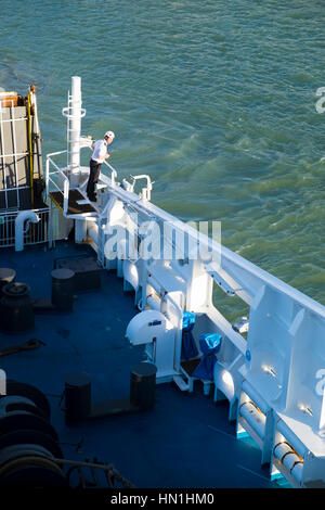 Ferry crew member checking clearance to side of boat leaving harbour - Stock Image