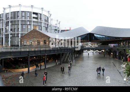 Gasholders modern apartment building and people shopping in Coal Drops Yard redevelopment & shopping area December Kings Cross London UK KATHY DEWITT - Stock Image